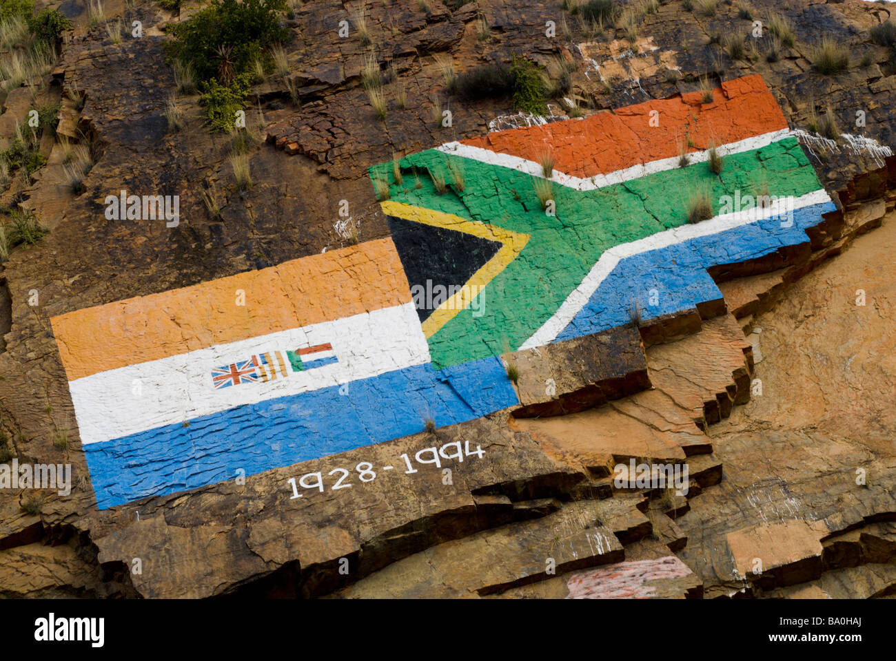 Painting on a rock face depicting new and old south African Flags Steytlerville Western Cape Province South Africa - Stock Image