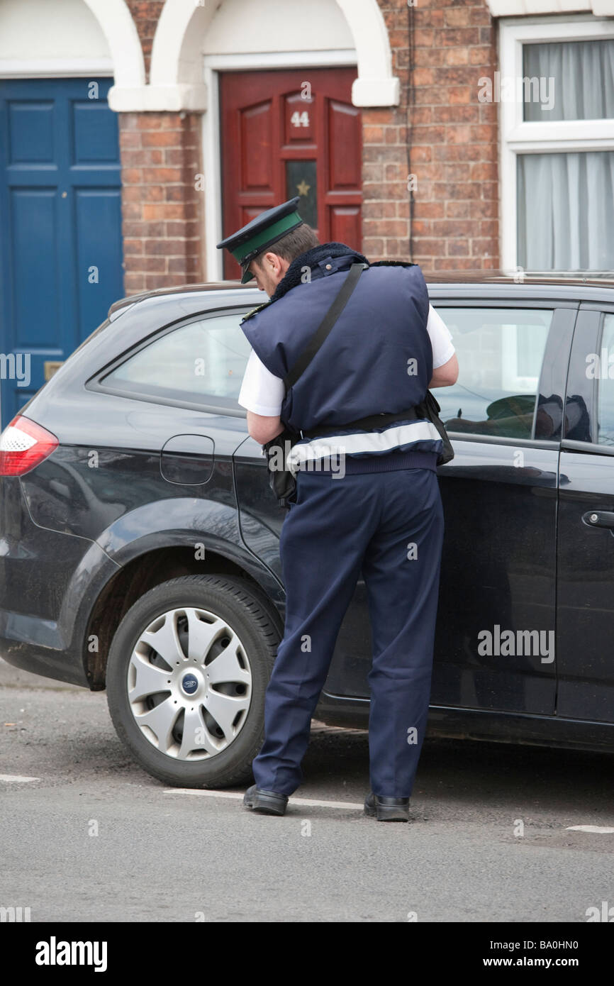 UK traffic warden / parking attendant inspects and notes details of a vehicle parked on the road - Stock Image
