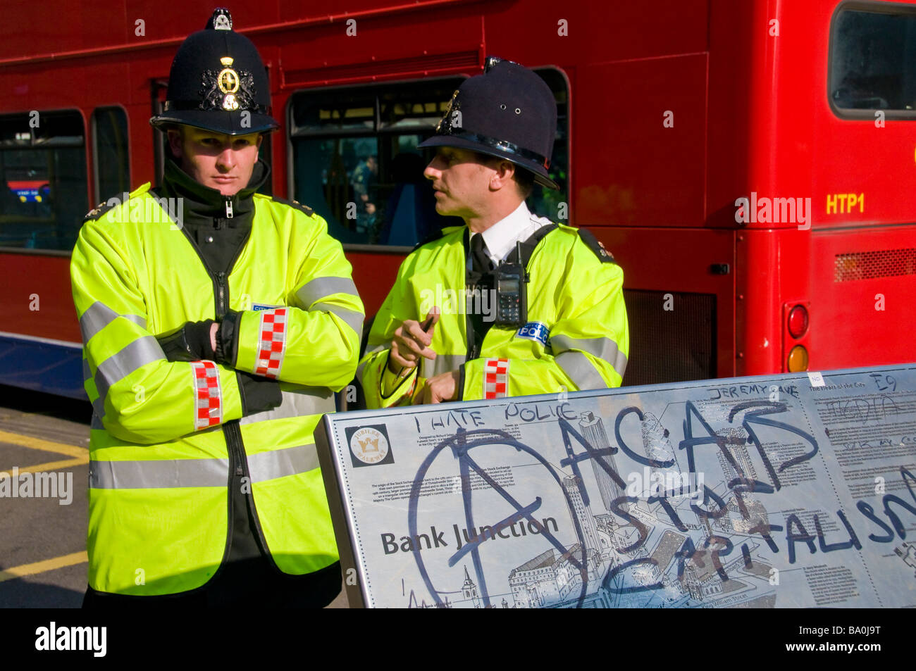 Two policemen standing by the Bank Junction sign with anti-capitalism graffitti, G20 Summit protests, London, England, - Stock Image