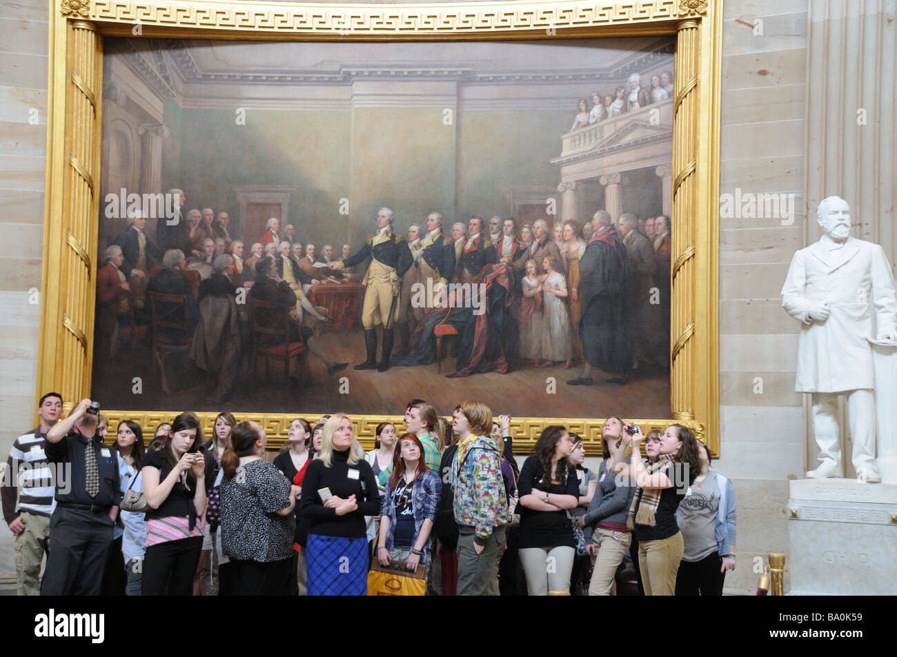 Visitors to the Rotunda of the U. S. Capitol building in Washington, D. C. see paintings of scenes from American - Stock Image