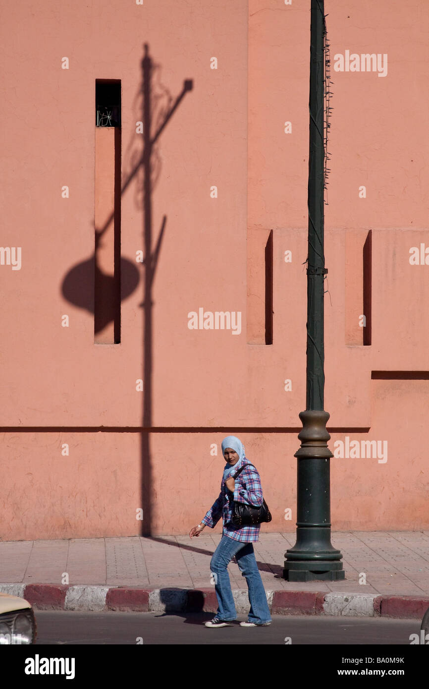 Young muslim arab woman crossing the street with traditional salmon pink walls in background and shadows cast by - Stock Image