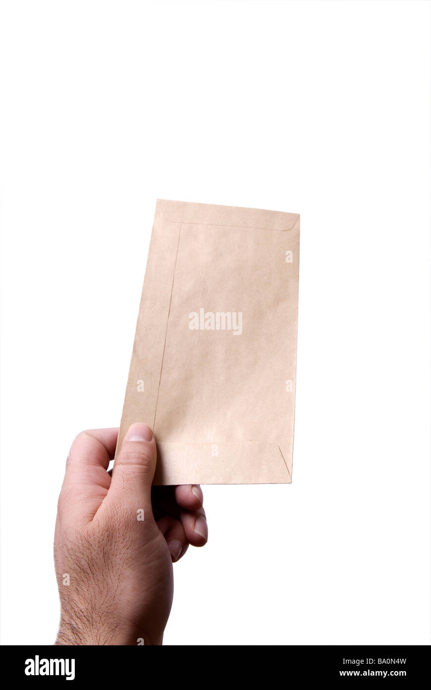 Hand holding a brown envelope against a white background - Stock Image