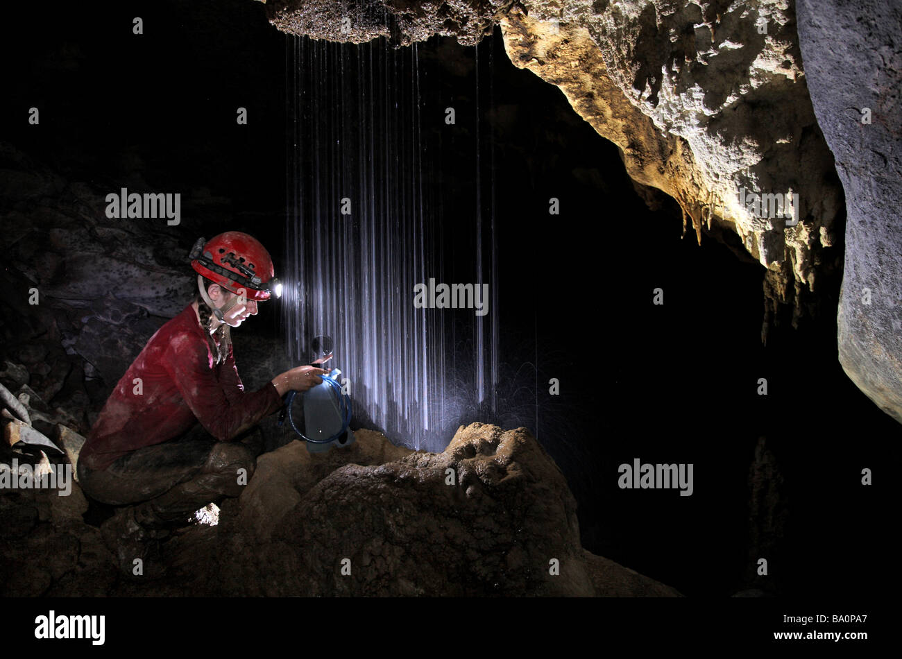 Young cave explorer filling her water container from a natural shower deep underground in Mulu National Park - Stock Image