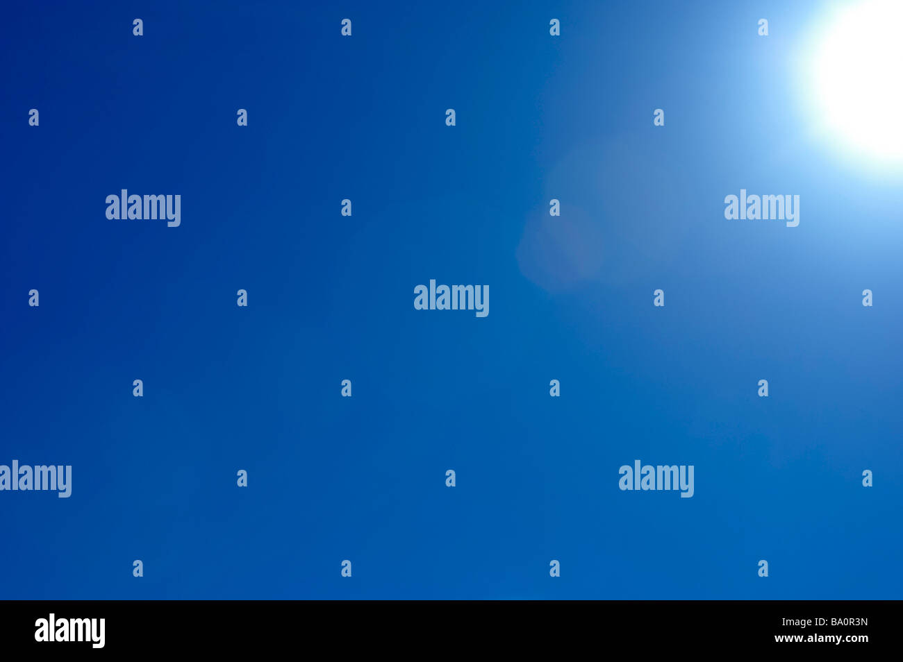Sun flare in blue sky - Stock Image