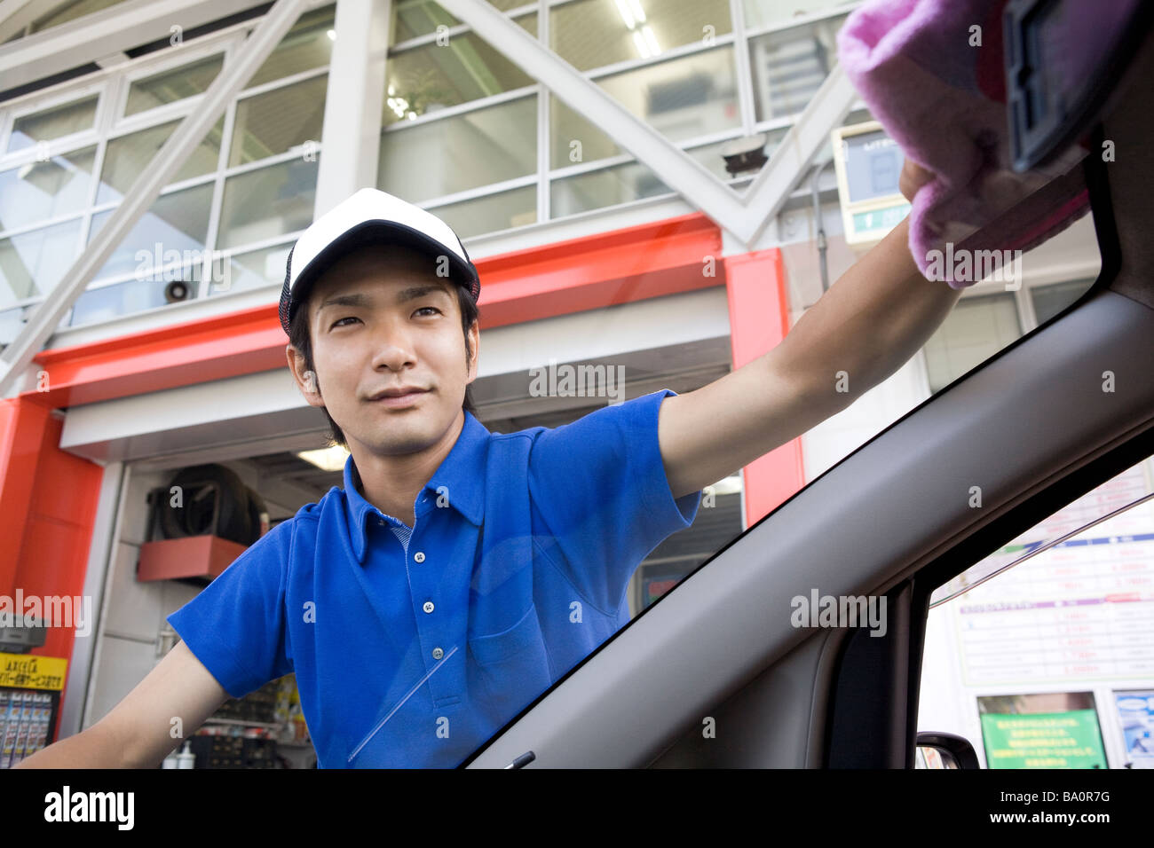 gas station clerk wiping car window stock image