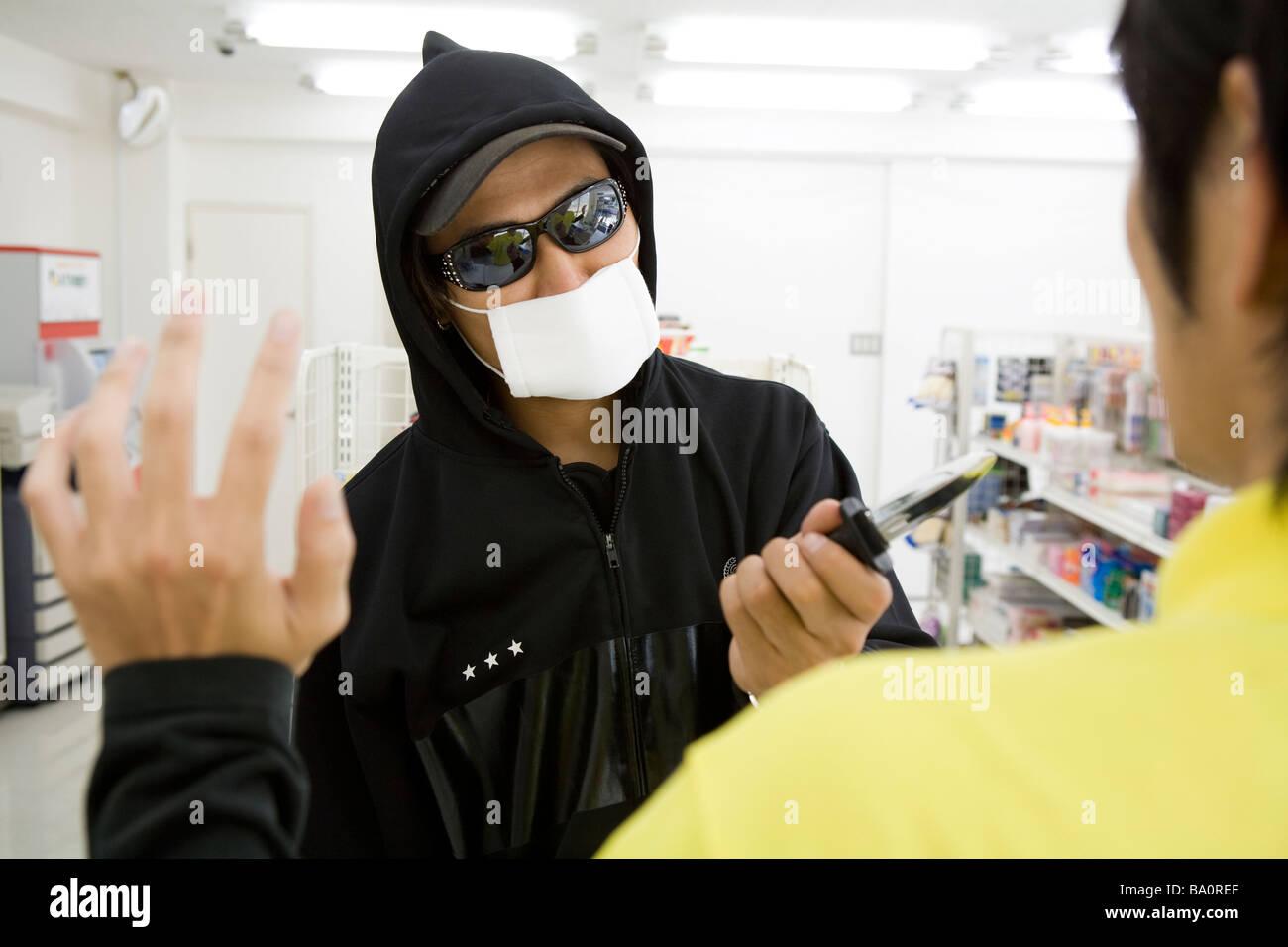 Robber threatening convenience store clerk - Stock Image