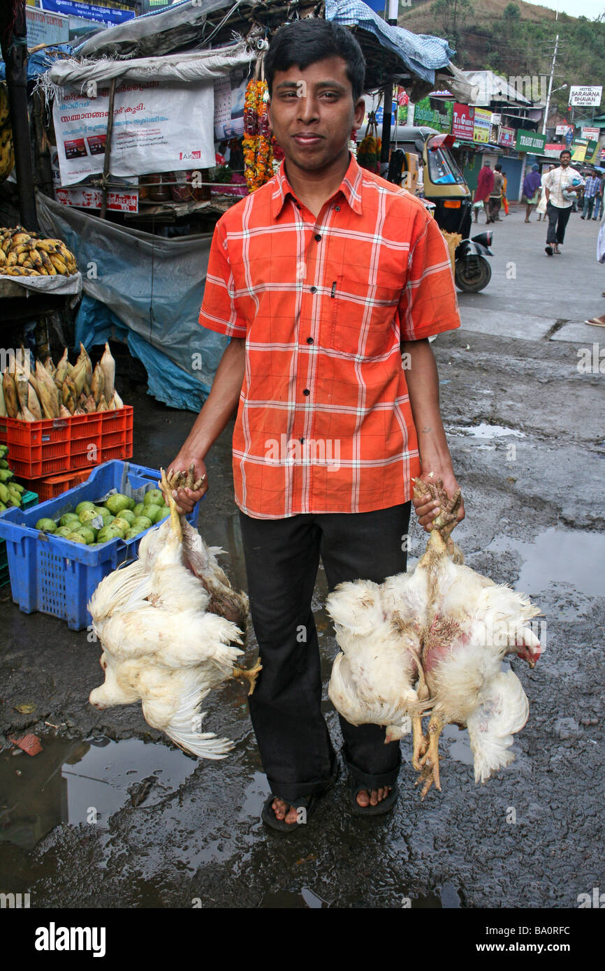 Young Indian Boy Carrying Chickens in Each Hand Through A Market - Stock Image