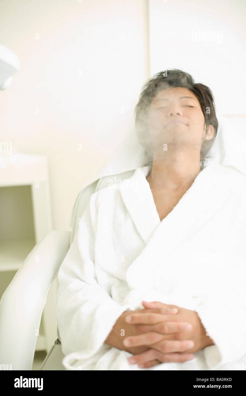 Young man receiving esthetic facial steam - Stock Image