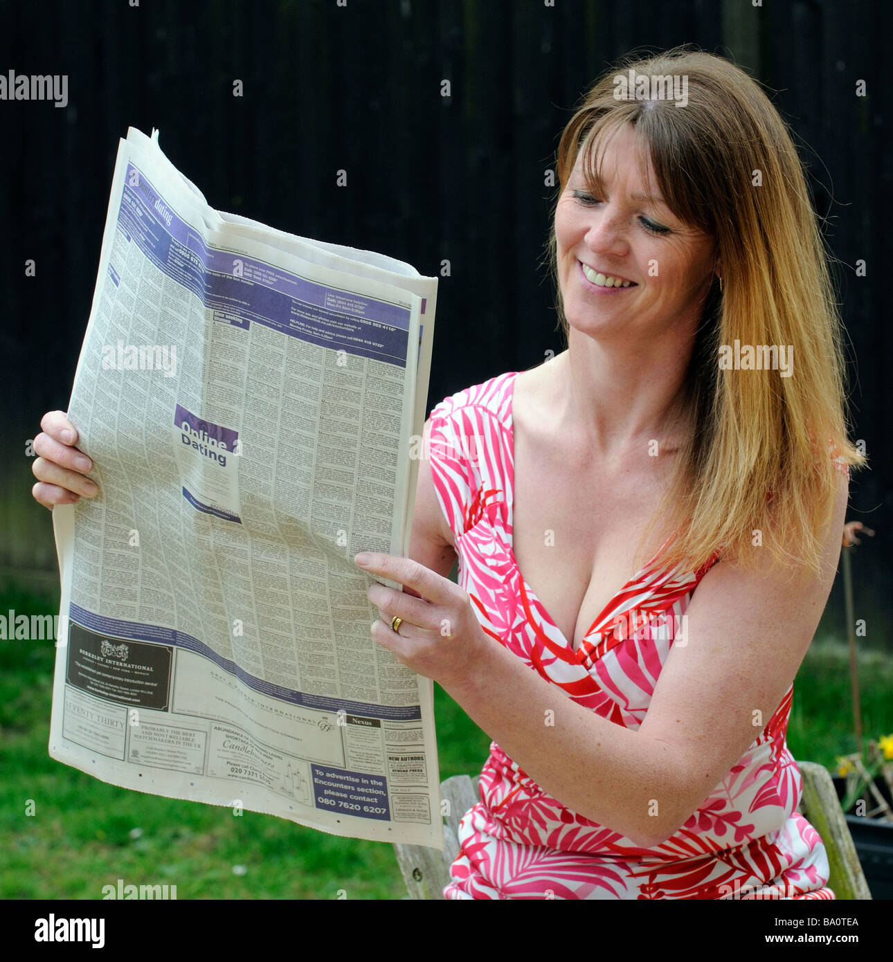 Woman reading small ads in newspaper - Stock Image