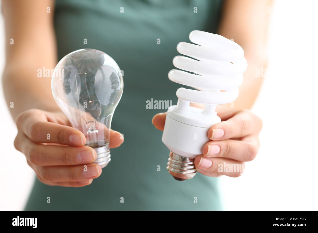Hands holding traditional and energy efficient light bulbs - Stock Image