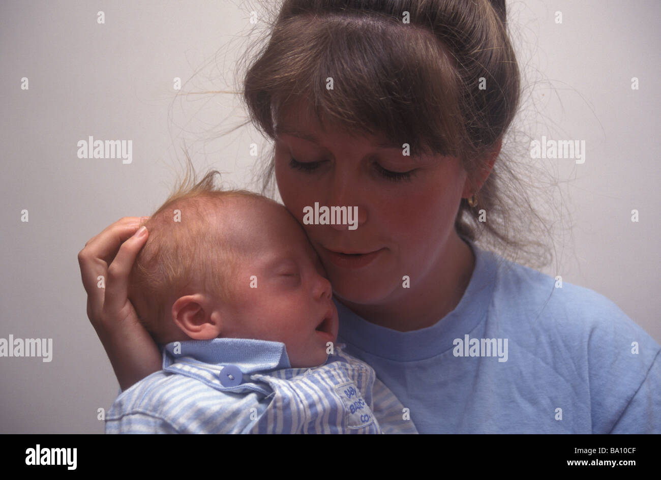 mother cradling her down s syndrome baby - Stock Image