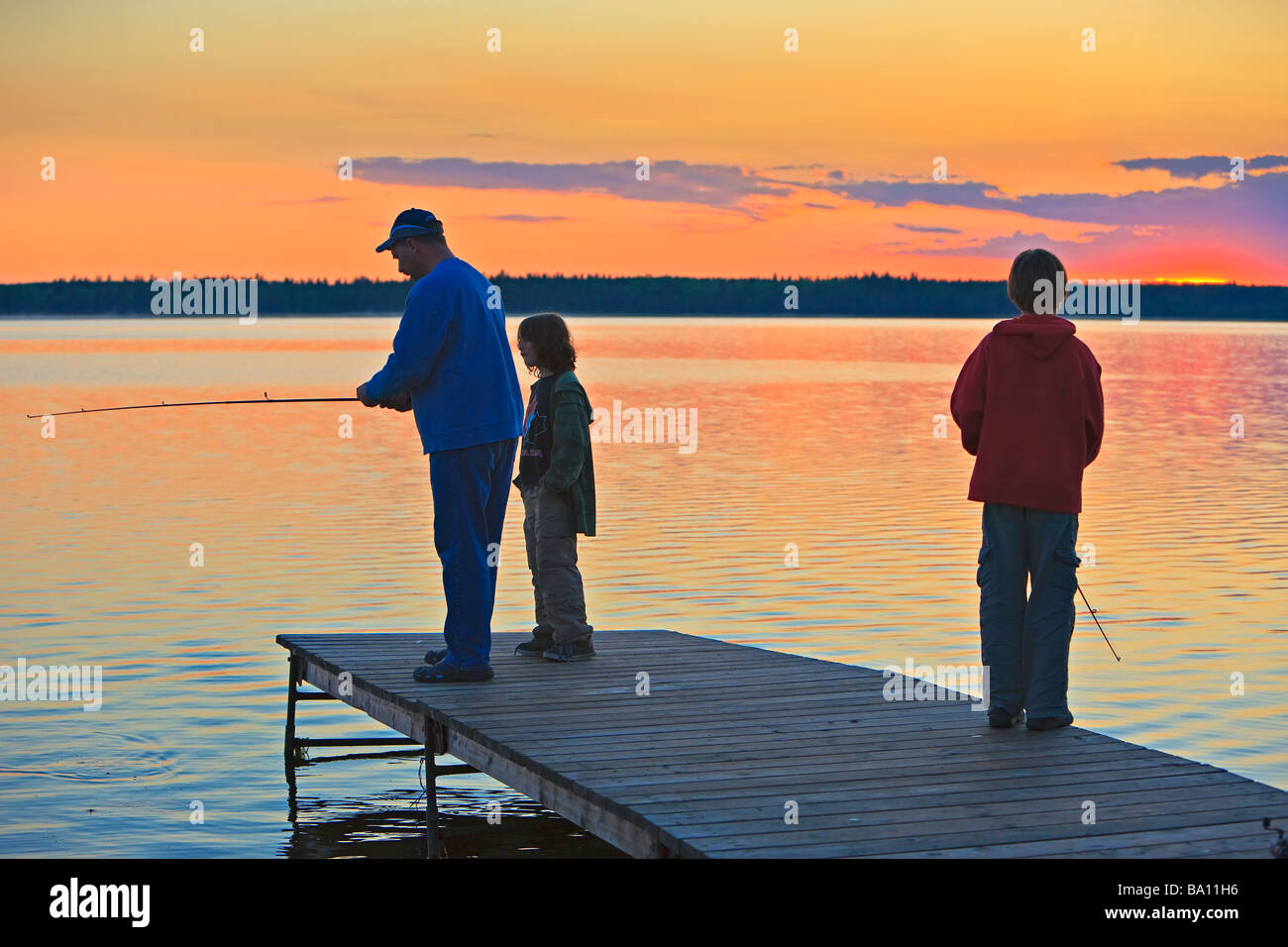 A Father with his two sons fishing at the end of a wharf on Lake Audy at sunset,Riding Mountain National Park,Manitoba,Canada. - Stock Image