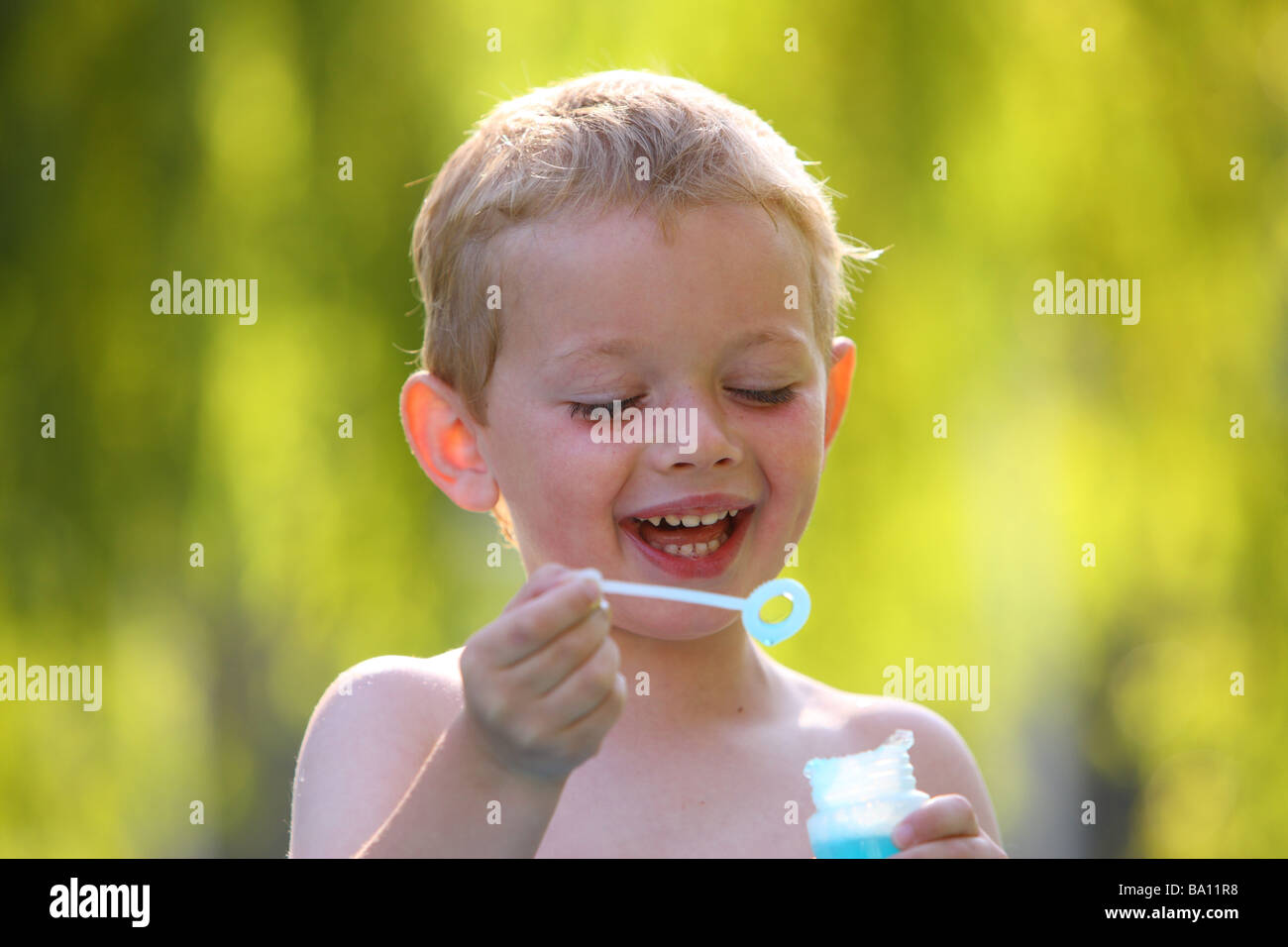 Young boy outside with bubble wand - Stock Image