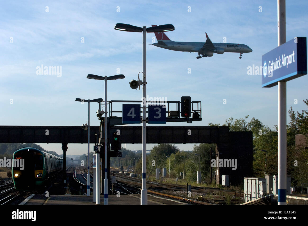 A North West Airways Jet Airplane lands above the railway station at Gatwick Airport as a train arrives - Stock Image