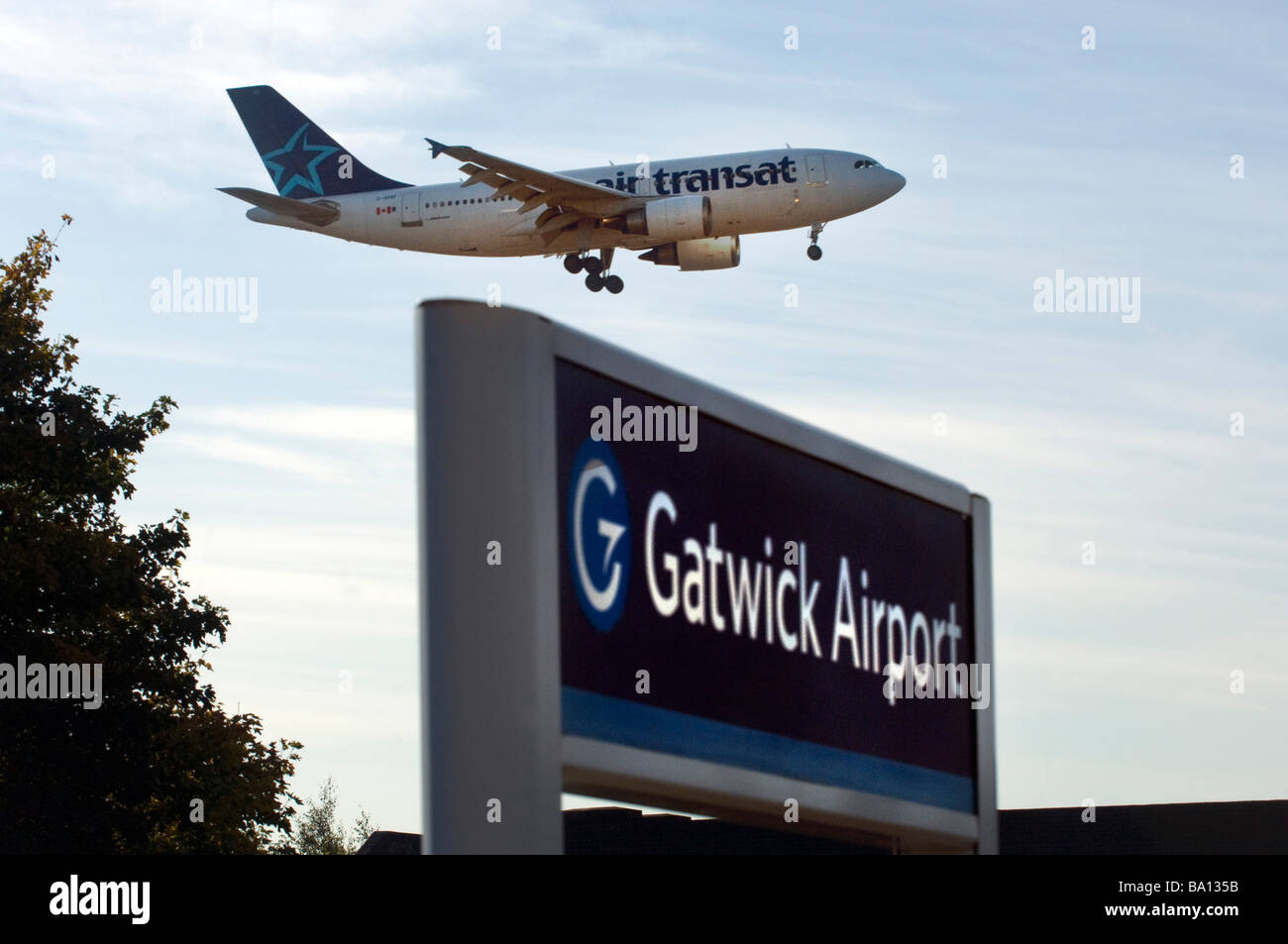 The landing wheels are down as a Air Transat Canadian Jet Airplane lands above the railway station at London Gatwick - Stock Image