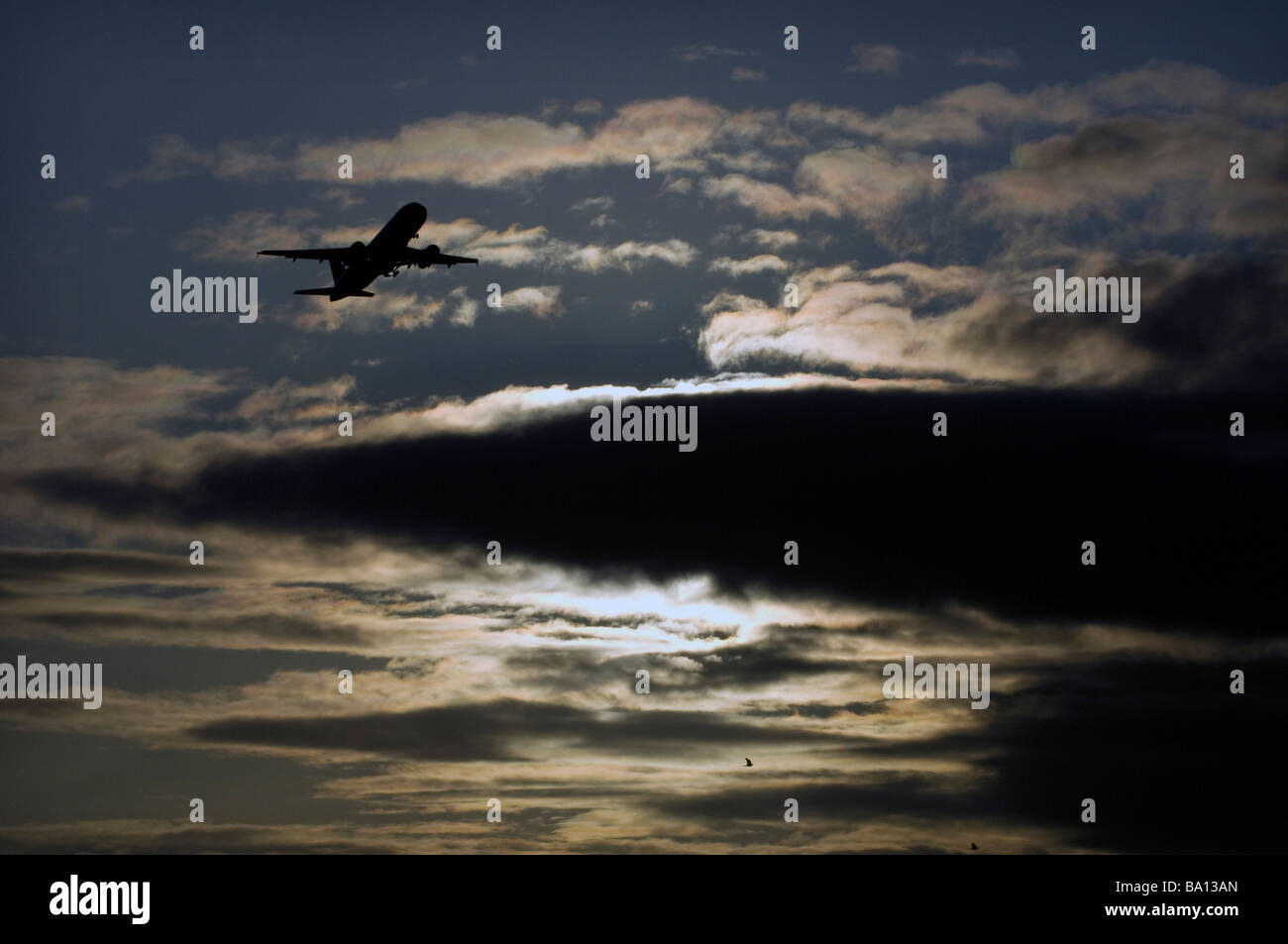 A a Jet Airplane takes off into a Cirrus cloud sky at dawn from Gatwick airport UK - Stock Image