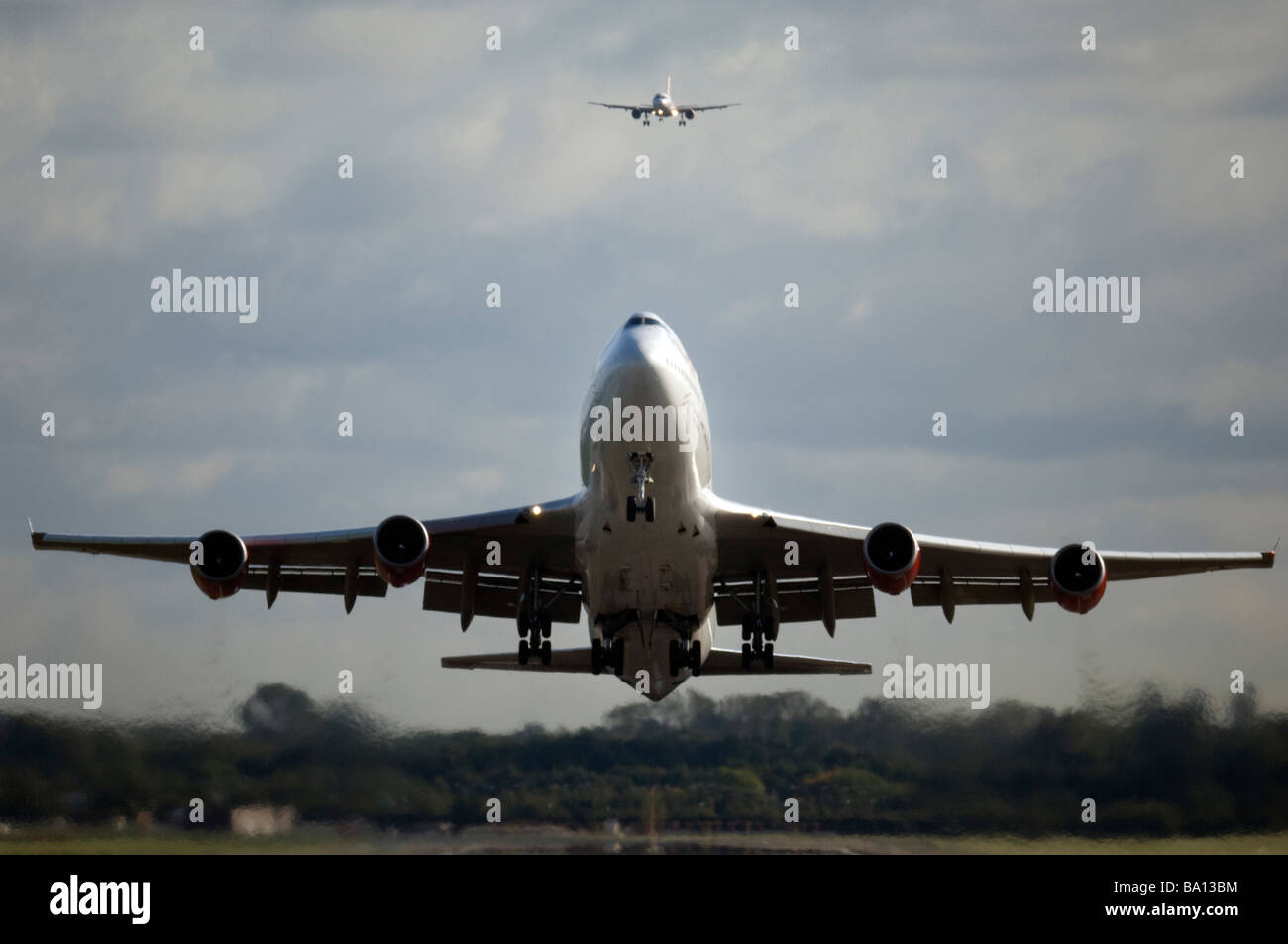 Virgin Atlantic Boeing 747 Jet Airplane takes off from Gatwick airport West Sussex with a smaller jet coming into - Stock Image