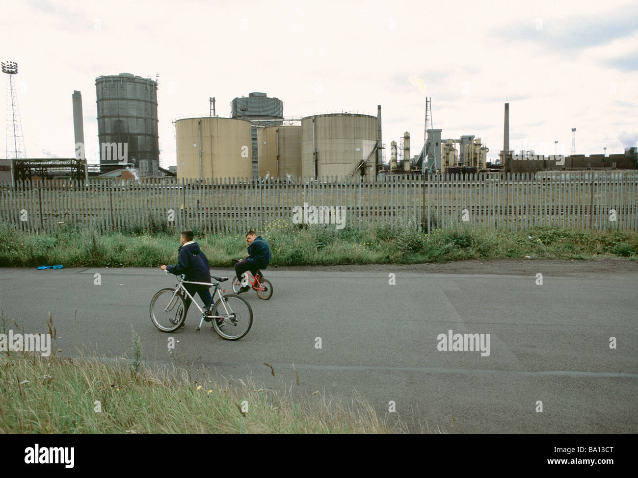 Two boys cycling past Redcar Steelworks Teesside Stock Photo