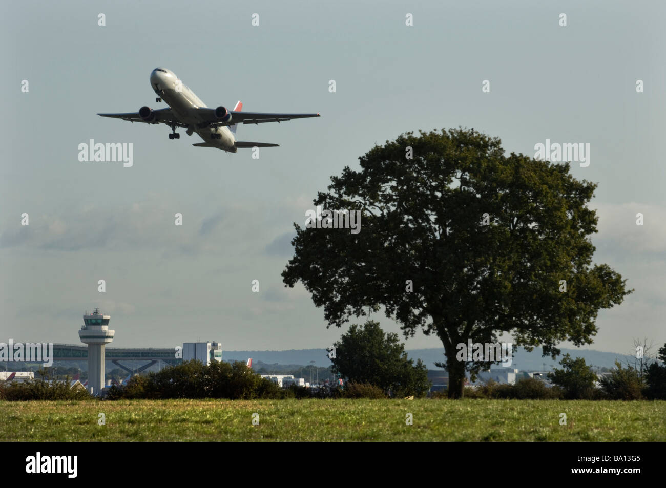 Delta Airbus Jet Airplane takes off over an Oak tree and the Gatwick control tower - Stock Image