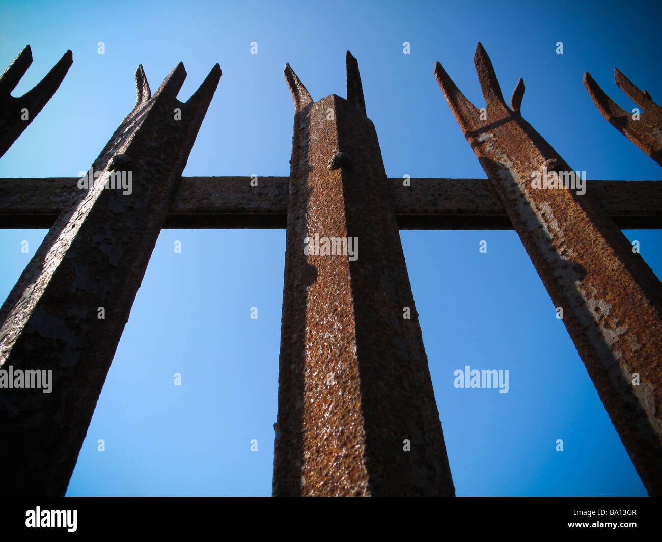 Top of rusty palisade security fence - Stock Image
