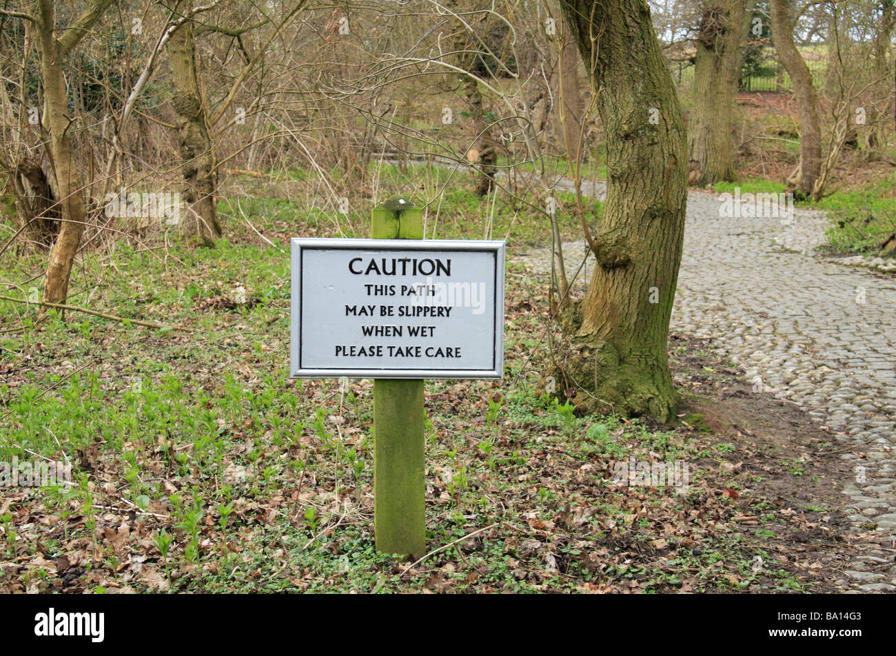 A standard National Trust sign 'This path may be slippery when wet' in Runnymede Surrey. - Stock Image