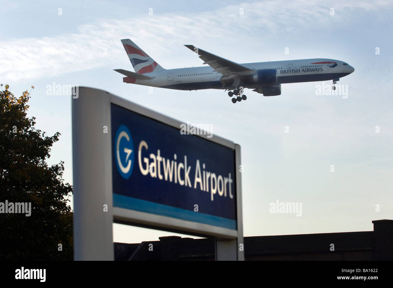 The landing wheels are down as a British Airways Jet Airplane lands above the railway station at Gatwick Airport. - Stock Image