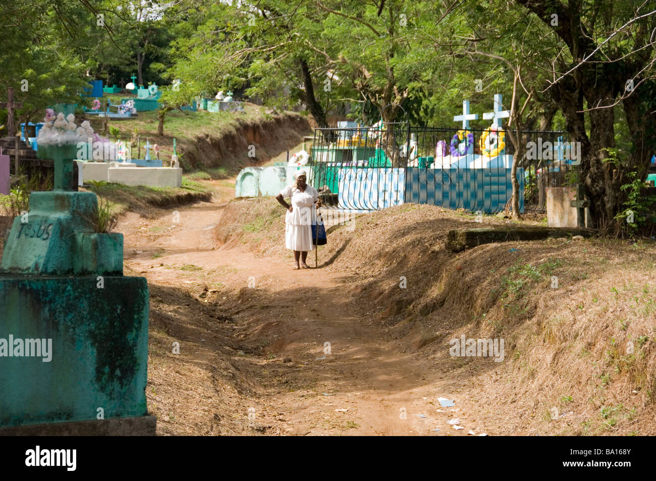 Garifuna woman dressed in white visits the cemetery in Livingston, Guatemala. - Stock Image