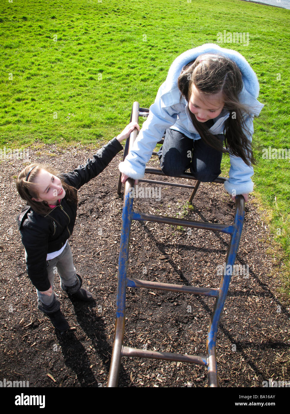 Big sister helping little sister on climbing frame Stock Photo ...