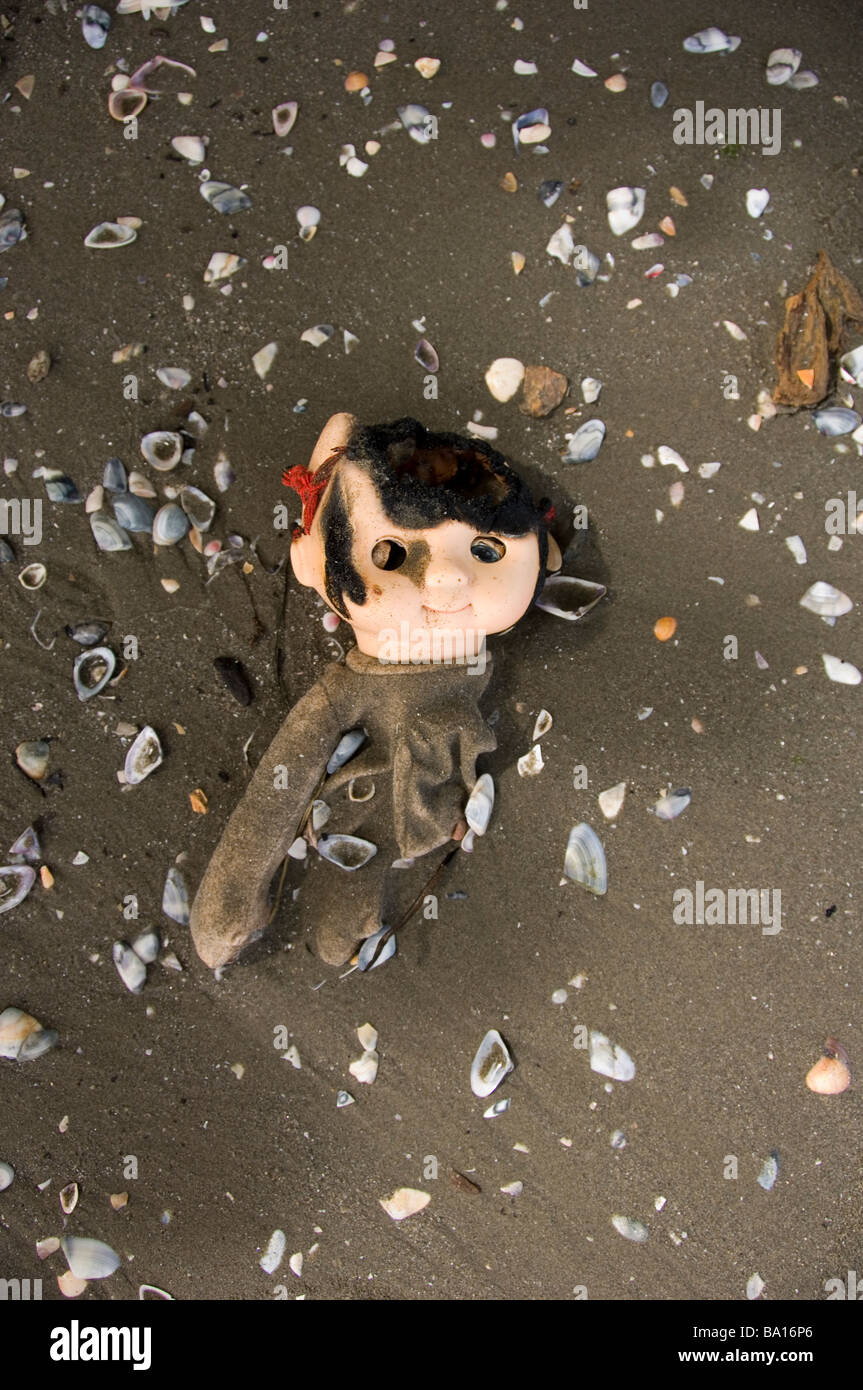 Burned doll on the beach - Stock Image