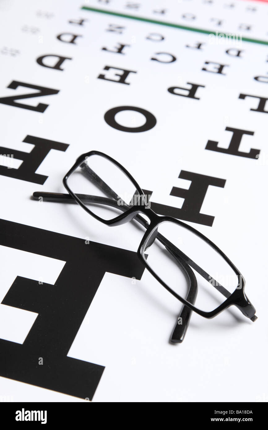 Glasses on eye chart - Stock Image