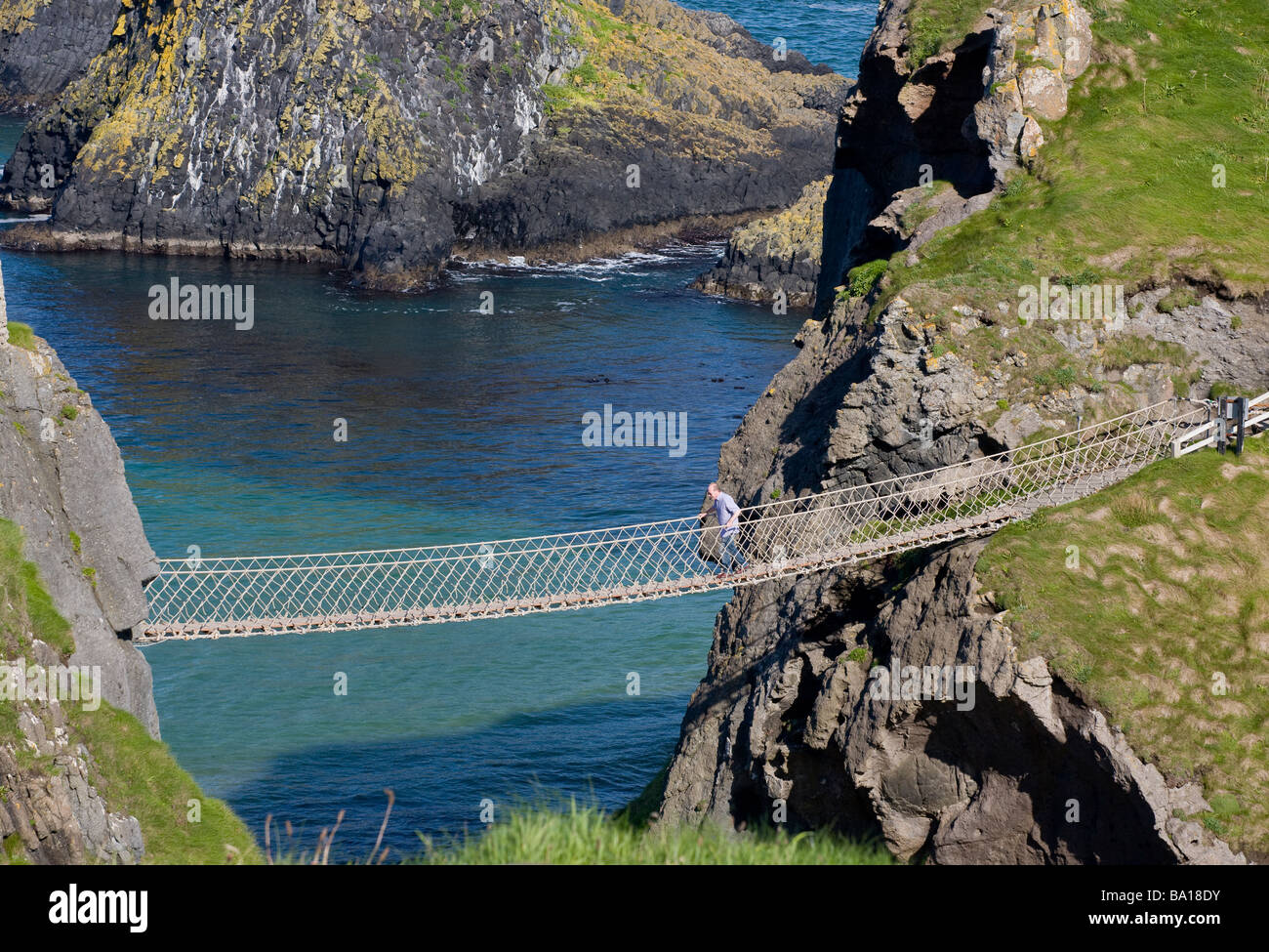 The return trip. A tourist crosses the famous rope bridge over the bright blue and green water from the island  - Stock Image