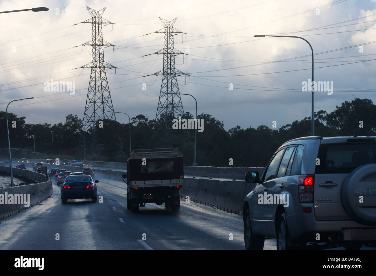 Cars driving down wet road - Stock Image