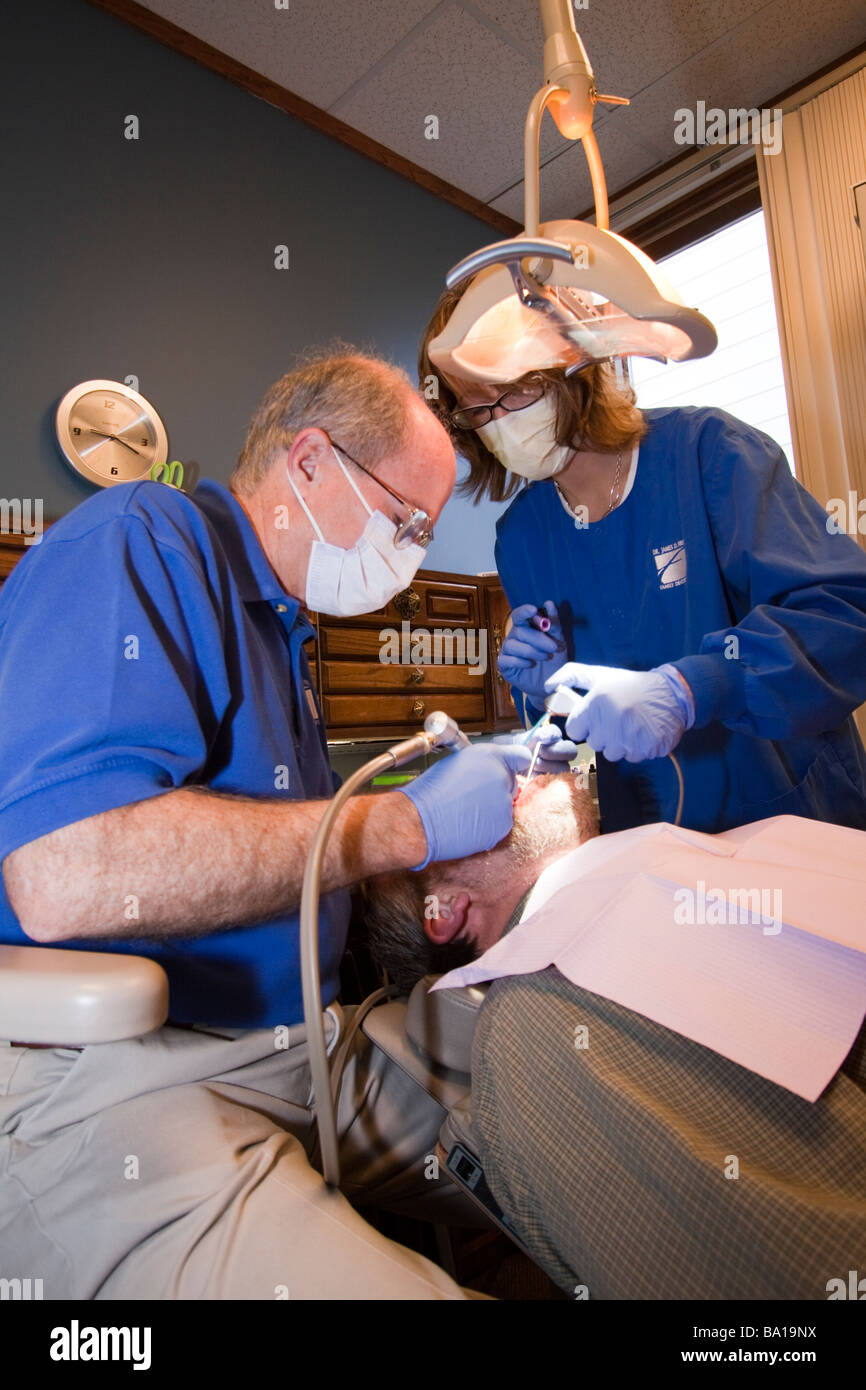 Dentist and assistant treating a patient in a dentist's chair. - Stock Image