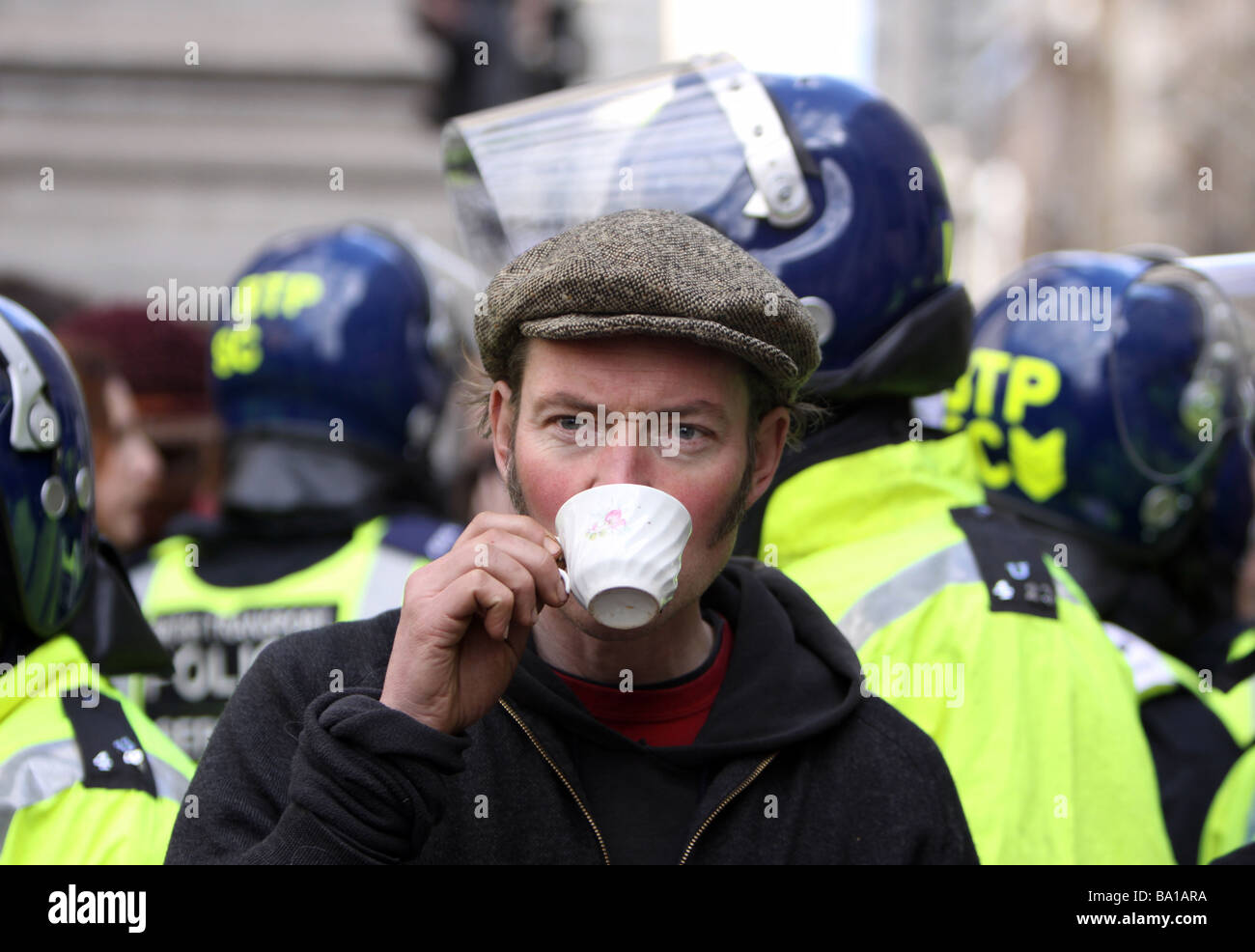 A protestor enjoys a cup of tea in front of a line of riot police at the G20 protests in London - Stock Image
