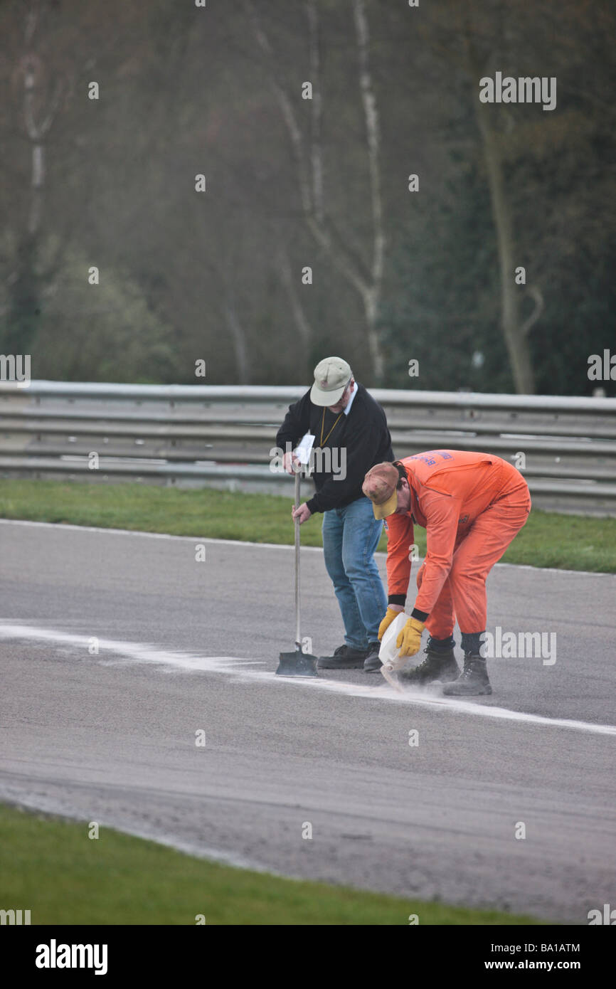 750 Motor club Historic Formula Junior championship race Plaster dust is applied to the track by marshalls to soak - Stock Image