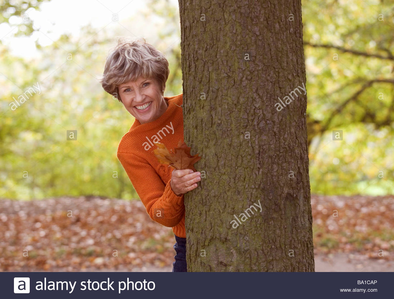 A senior woman standing next to a tree smiling - Stock Image