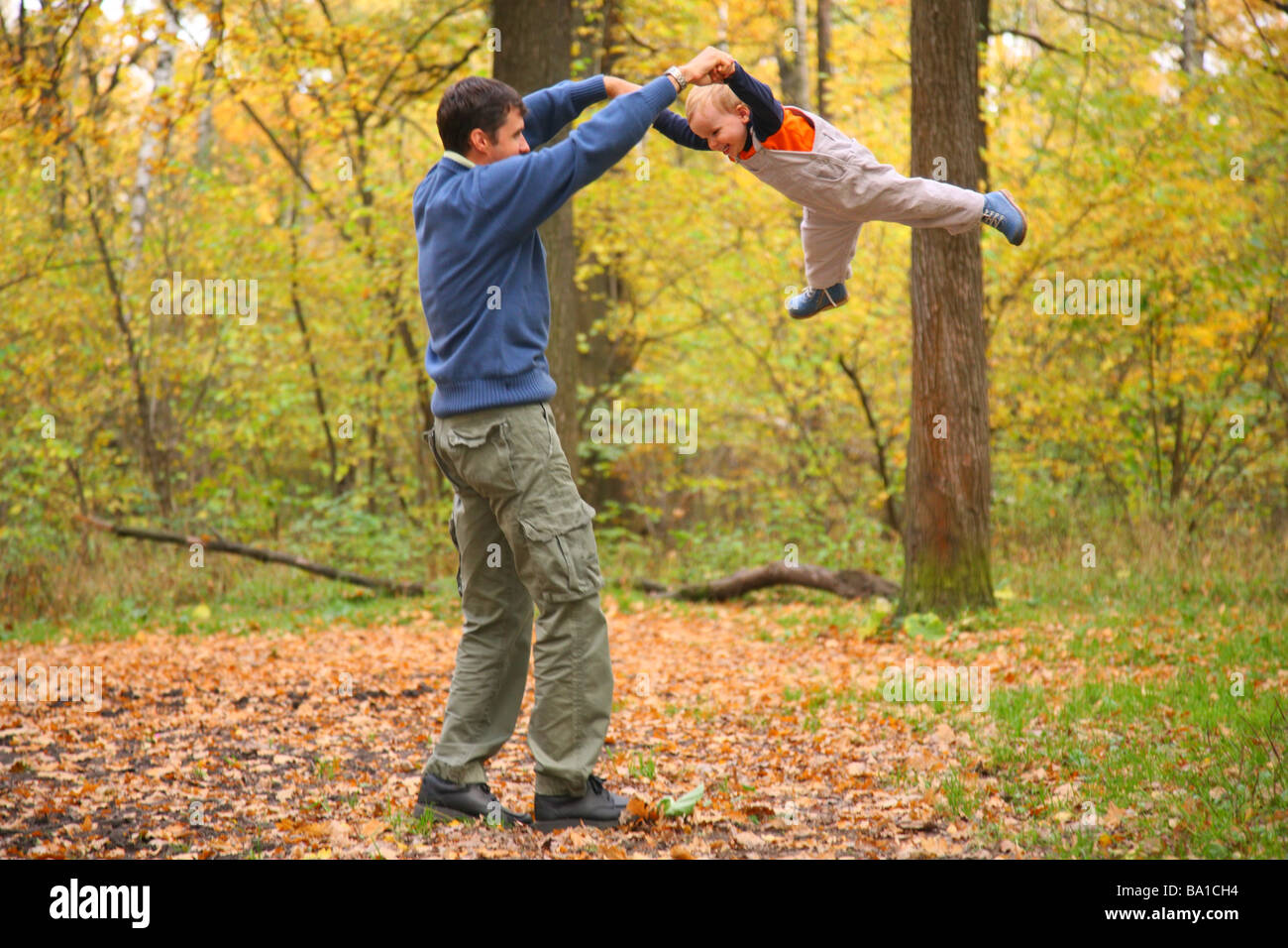 Father rotates child for hands in wood - Stock Image