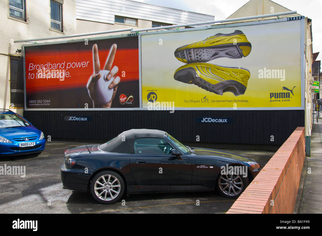 JCDecaux advertising billboards for Virgin Media broadband and Puma trainers on private car park in Cardiff South - Stock Image