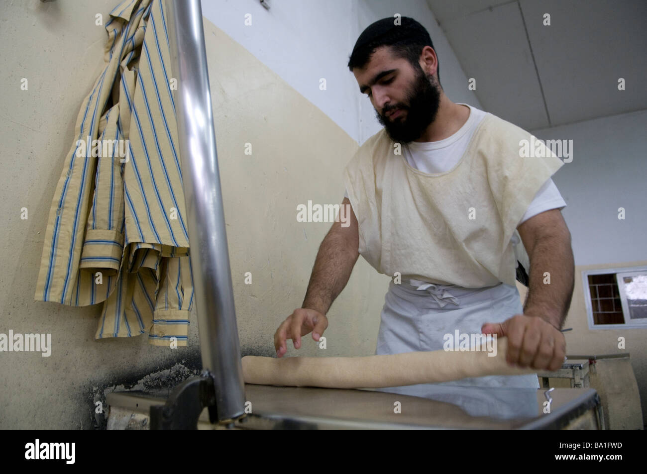 A religious Jew preparing Matzah traditional handmade Passover unleavened bread in Kfar Chabad or Habad village - Stock Image