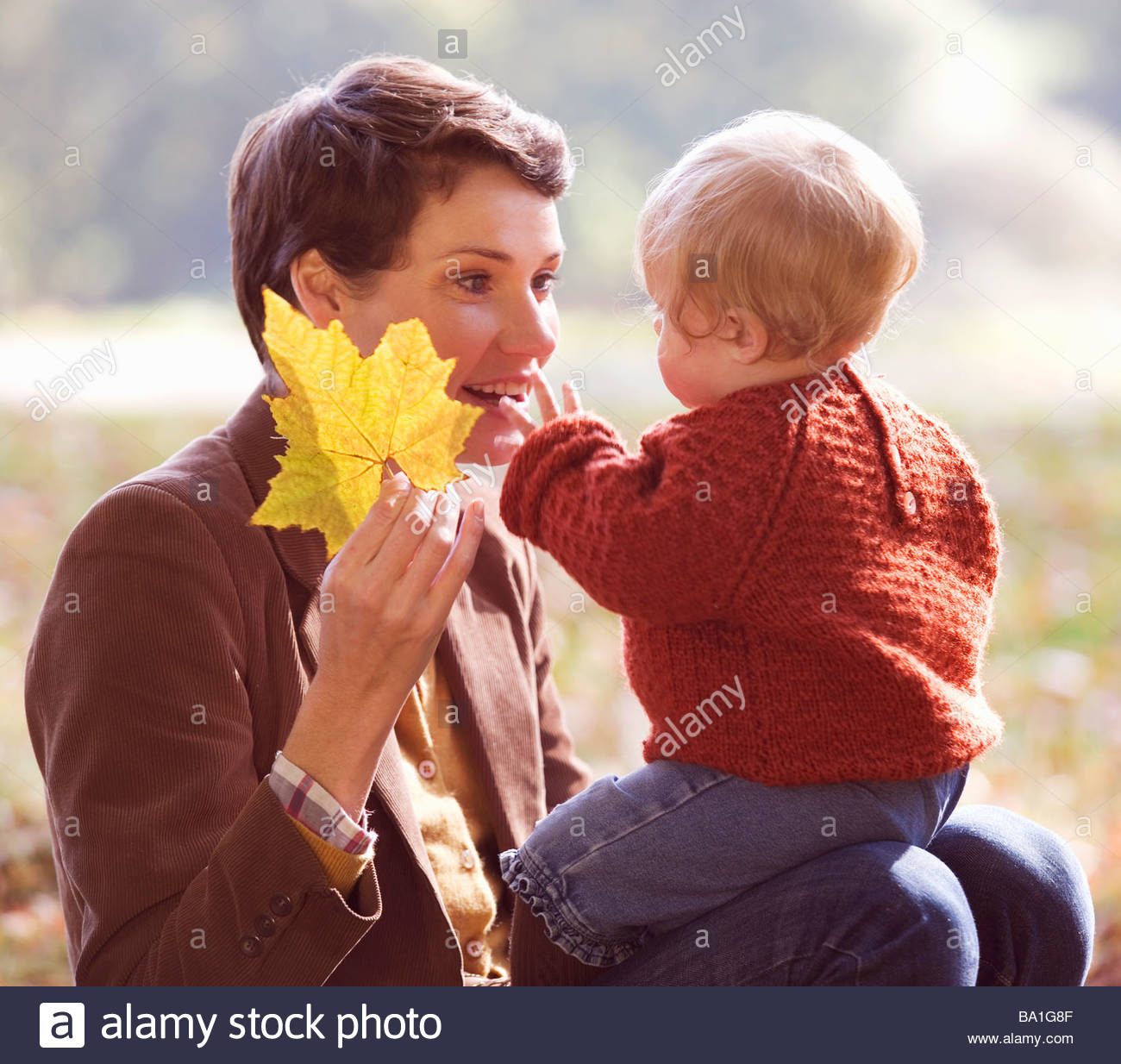 A young mother showing an autumn leaf to her baby Stock Photo