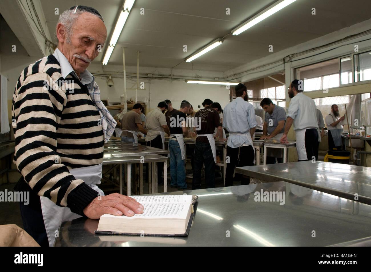 A religious jew prays as other orthodox Jews prepare Matzah traditional handmade Passover unleavened bread in Kfar - Stock Image