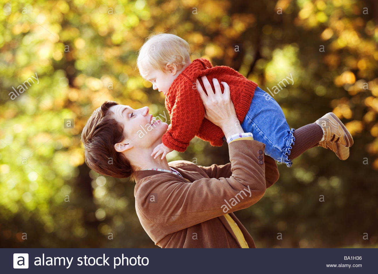 A young mother lifting her baby in the air playfully - Stock Image