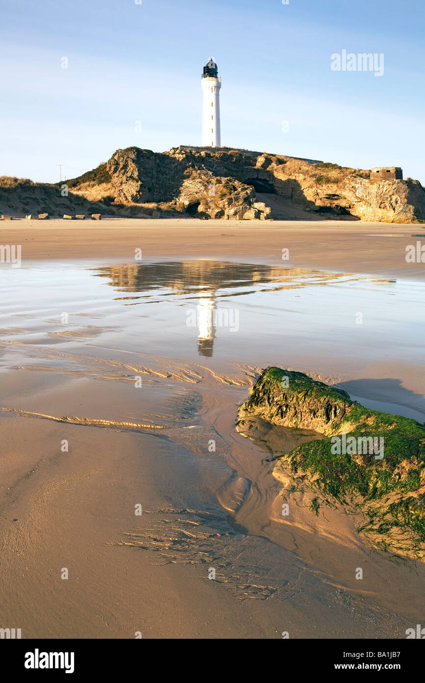 The early morning wet sand of low tide reflects a lighthouse and a seaweed topped rock points towards it like a - Stock Image