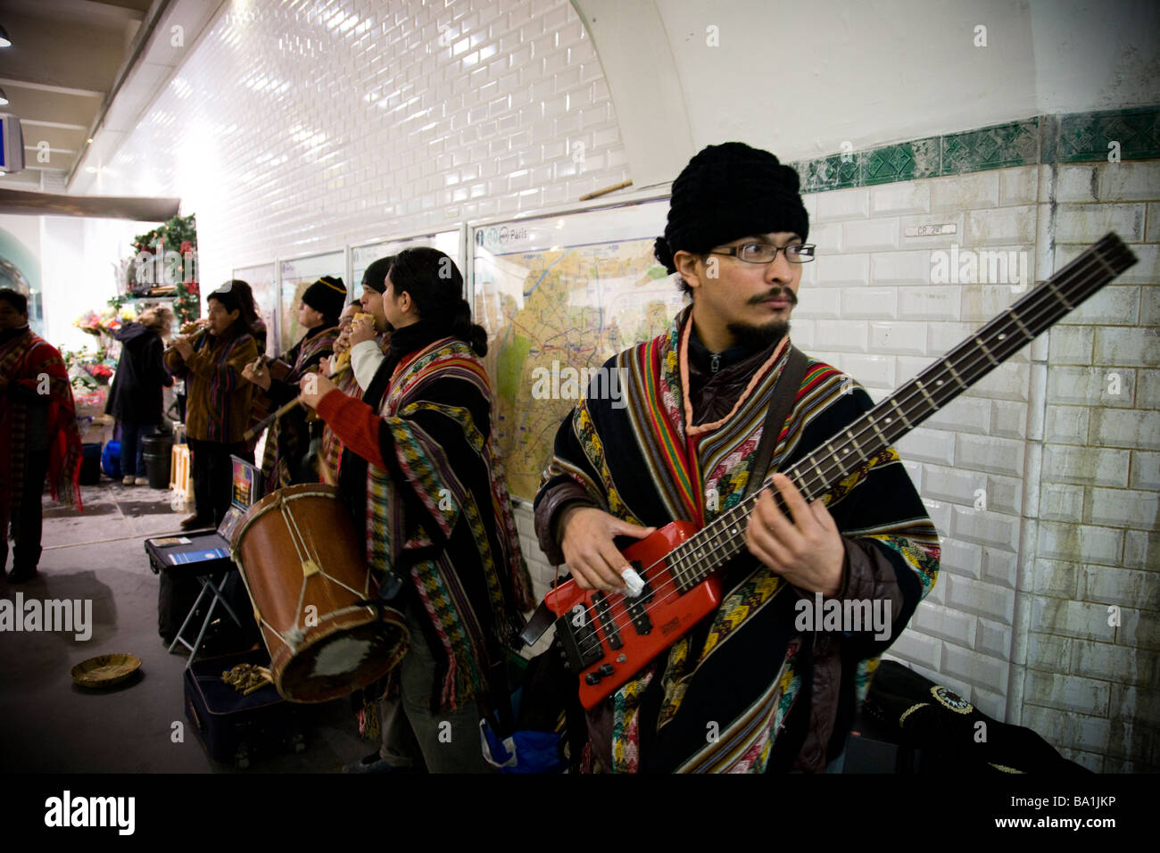 A South American band busks in a busy Parisian underground station - Stock Image