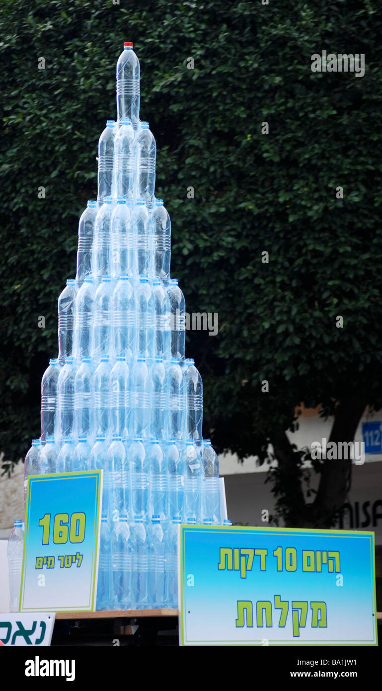 Save water display showing mineral water bottles containing 160 litres which is the amount of water used in a 10 - Stock Image