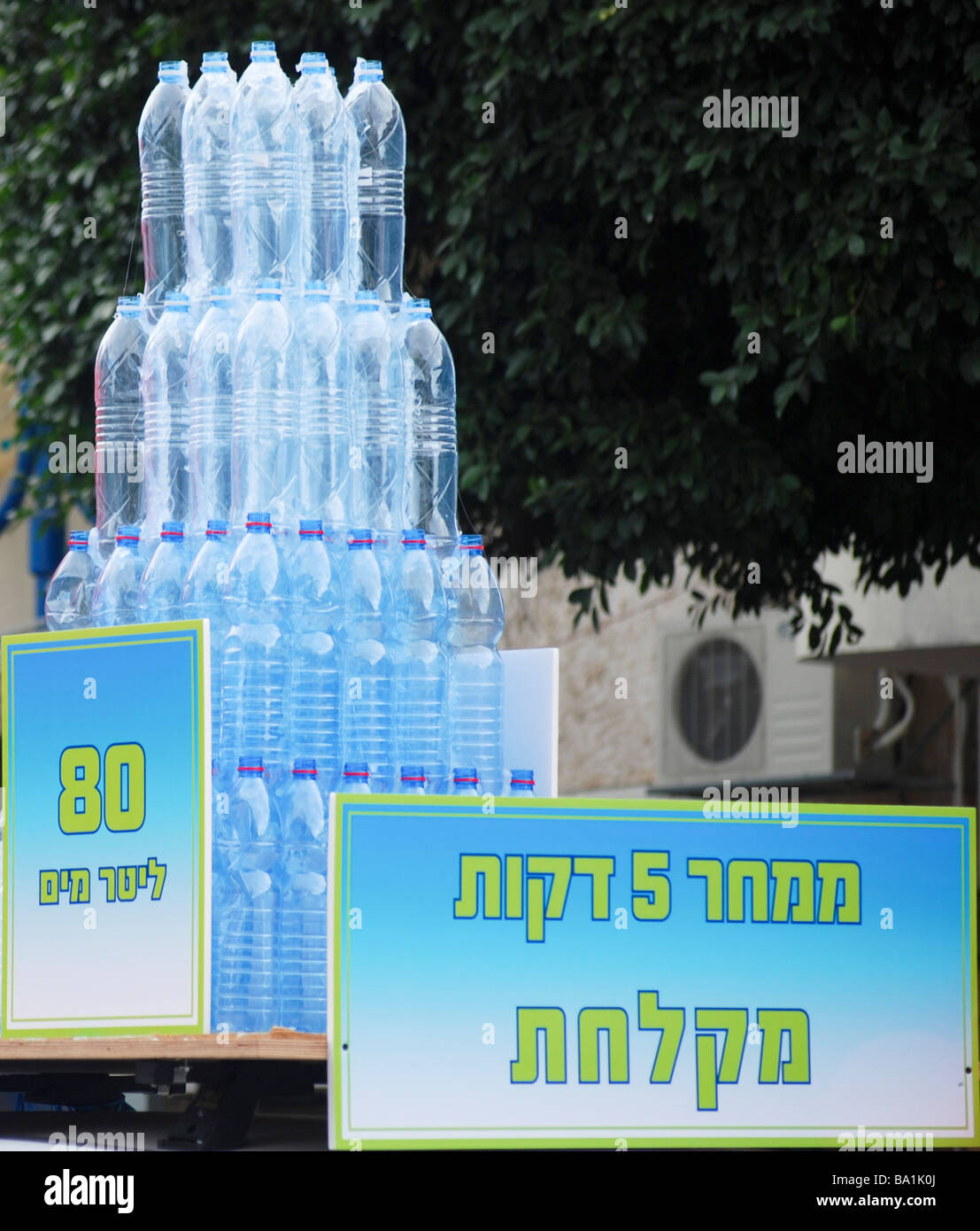 Save water display showing mineral water bottles containing 80 litres which is the amount of water used in a 5 minute - Stock Image