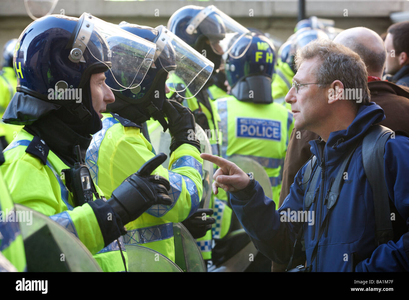 Demonstrator confronting policeman at G20 protests - Stock Image
