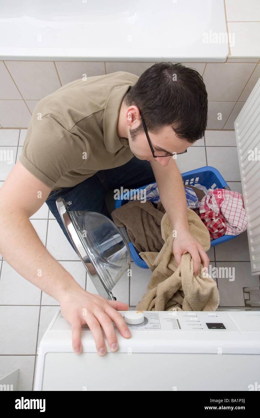Young man at the washing machine - Stock Image