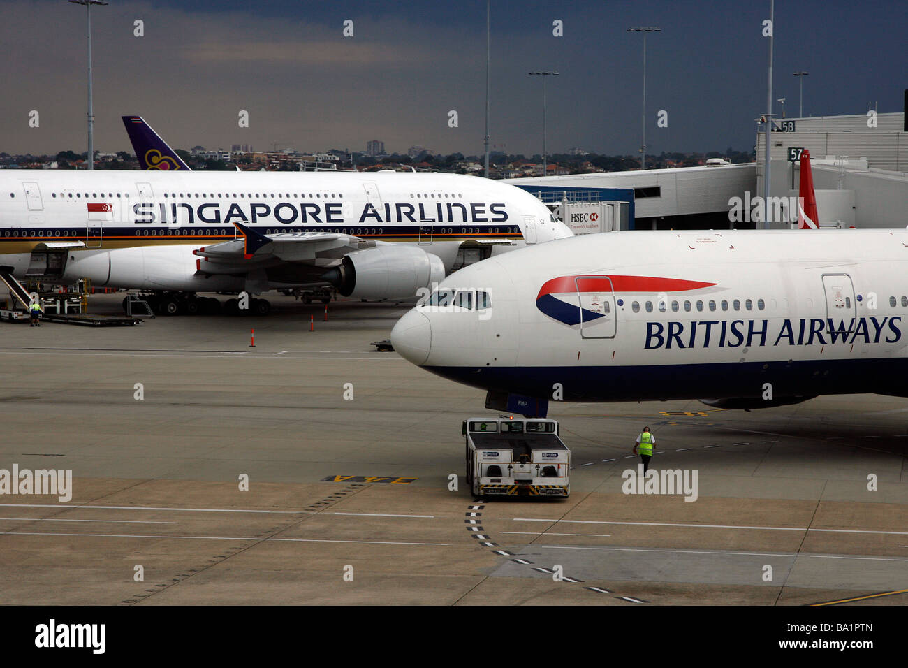 A British Airways Boeing 777-200 aircraft passes an Airbus A380 plane at Sydney Kingsford Smith International Airport - Stock Image