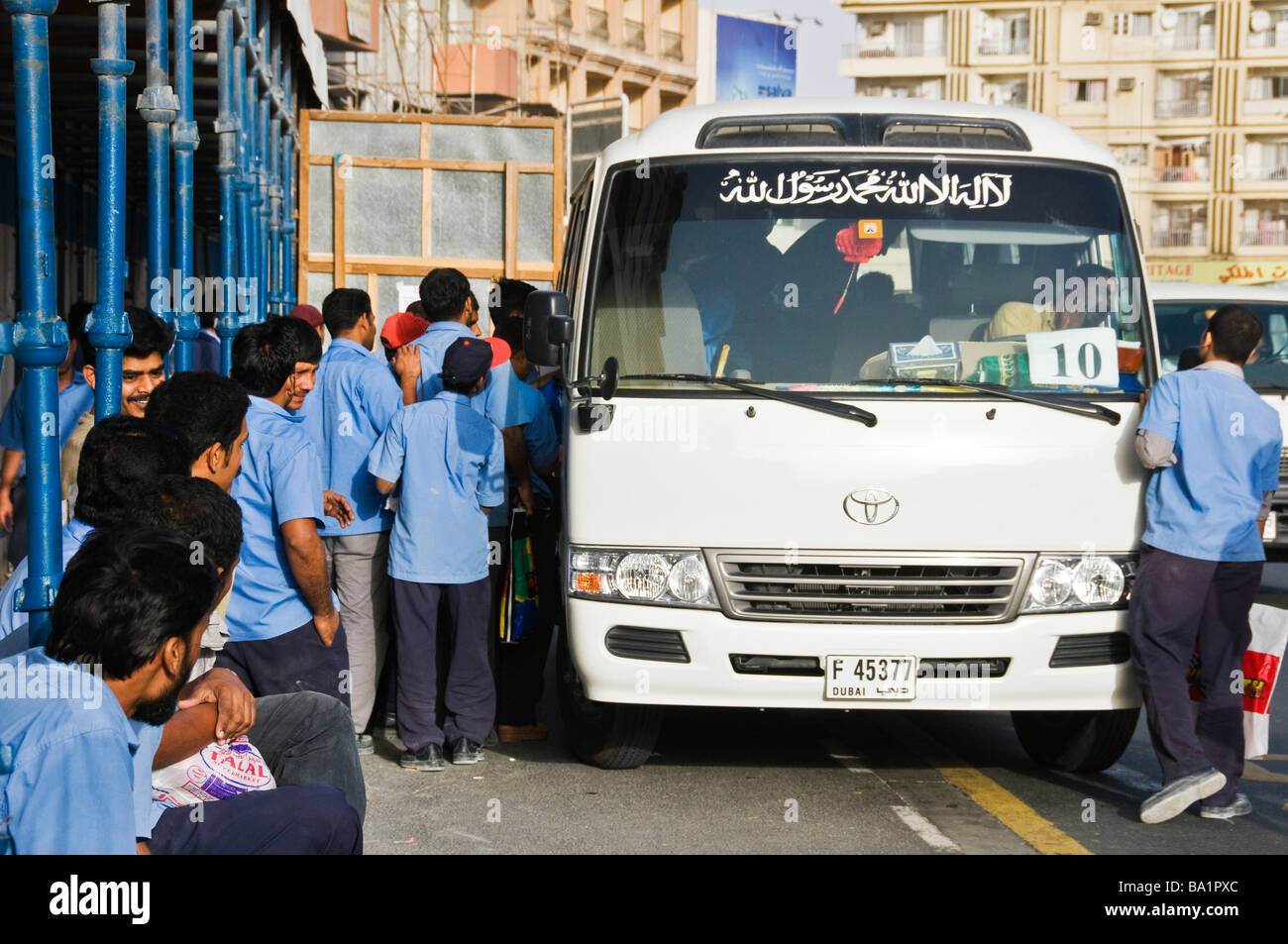 Foreign workers getting on a bus after a day of work Dubai UAE - Stock Image